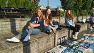 Zdjęcie absolwentów z książkami wyłożonymi do sprzedania - na trybunach boiska szkolnego.
