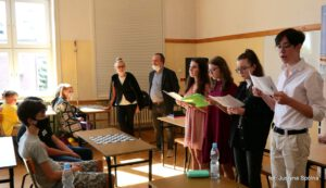 """Zdjęcie ukazuje jedną z grup uczniów czytających """"Zemstę"""""""
